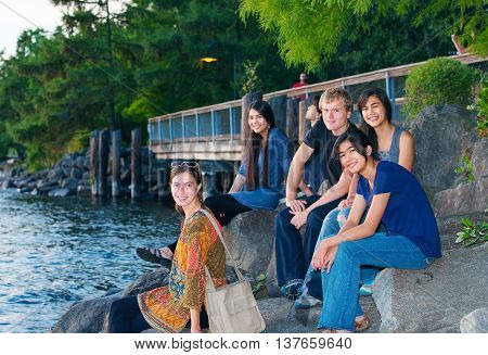 Multiethnic group of friends sitting on rocks by lake together