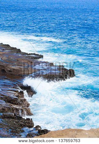 Beautiful tropical blue ocean water hitting against rocky edge along Hawaii's coast