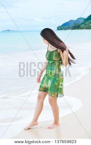 Beautiful biracial Asian Caucasian teen girl dipping toes in water on tropical Hawaiian beach