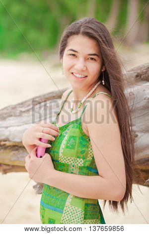 Beautiful biracial Asian Caucasian teen girl holding cellphone smiling on Hawaiian beach profile to camera