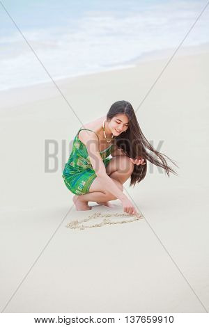 Beautiful biracial Asian Caucasian teen girl drawing heart in sand on tropical beach