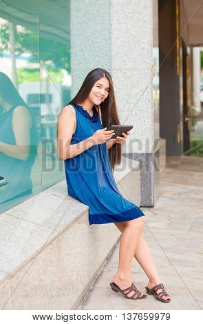 Beautiful biracial Asian Caucasian teen girl holding tablet computer sitting outside store window