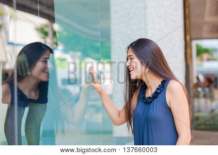 Biracial Asian Cuacasian teen girl window shopping in urban setting downtown looking in window with surprised and pleased expression