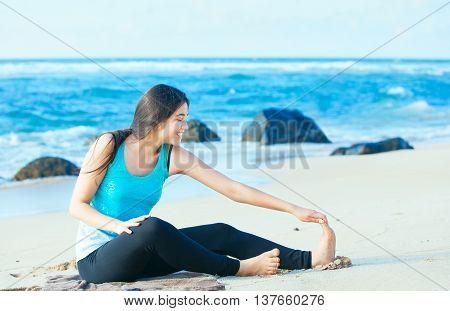 Beautiful biracial Asian Caucasian teen girl stretching and exercising on beach