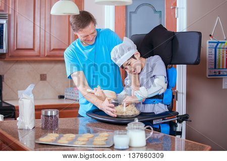 Caucasian father helping disabled son standing in medical stander to bake cookies in the kitchen.