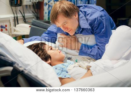 Handsome Caucasian father leaning over hospital bed talking to his young disabled biracial son sick in the hospital. Child has cerebral palsy
