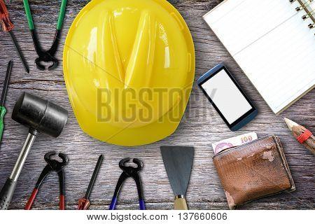 Plastering trowel, hammer, screwdriver,Cream wire cutter,helmet,phone,notebook,pencil, wallet on the wooden floor