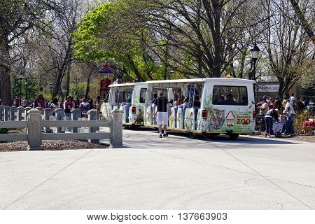 BROOKFIELD, ILLINOIS / UNITED STATES - APRIL 23, 2016:  Visitors to the Brookfield Zoo may board the zoo's open-air motor safari trams for a narrated tour of the zoo.