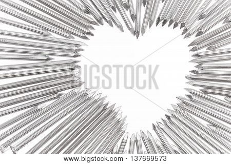 Steel concrete nails pointing the tips toward heart shape empty white space for text in the off center of the white background