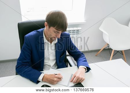 Man Writing In A Notebook In The Office