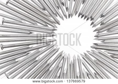 Steel concrete nails pointing the tips toward empty white space for text in the off center of the white background