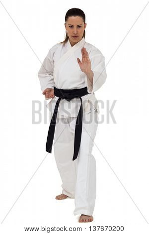 Portrait of female fighter performing karate stance on white background