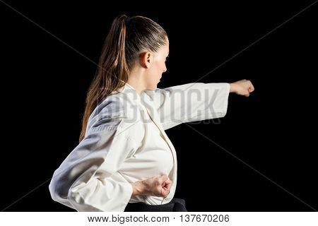 Female fighter performing karate stance on black background