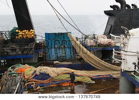 The Bering Sea Russia - Jun 18th 2016: The Bering Sea fishing seiner VLADIMIR STARZHINSKY the seaman to place a fishing net on a deck.