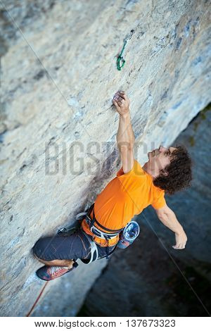 male rock climber. rock climber climbs on a rocky wall. a man hanging by one hand and resting. focus on the hand