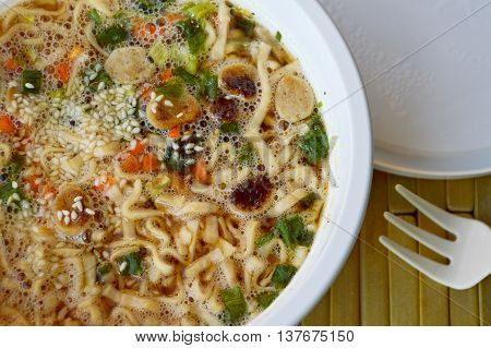 instant noodle soft boiled in plastic cup on bamboo plate