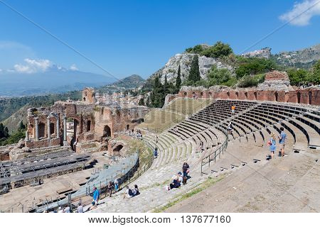 TAORMINA ITALY - MAY 17: Tourists visiting the ancient Greek theater of Taormina city while workers mounting a stage and the Etna is visible at the horizon on May 17 2016 in Taormina at the island Sicily Italy