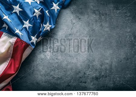 USA flag. American flag. American flag freely lying on concrete background. Close-up Studio shot. Toned Photo.