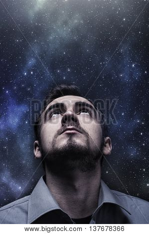 Young man looking up to the night sky
