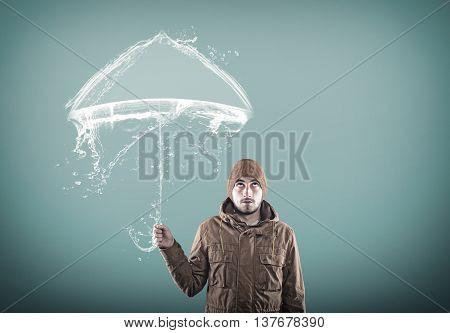 Young man using an umbrella made of water.