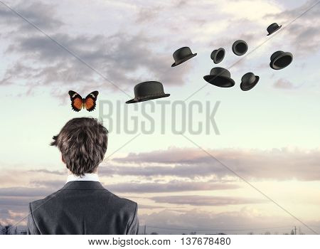 Businessman with a butterfly above his head while hats are flying around him.