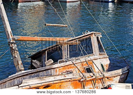 Half submerged small fishing boat in harbor