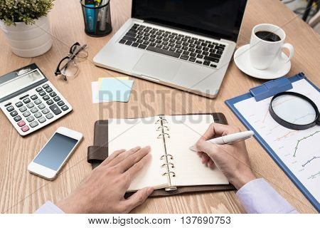 Image of business hands with pen over business document in working environment.  Man Analysis Business Accounting. Business graph analysis report on wood desk.