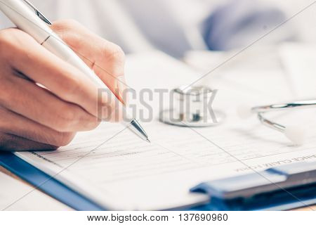 Female doctor filling medical form on clipboard