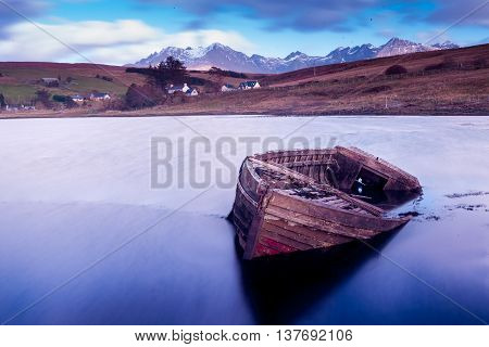 Abandoned boat in a beautiful lake with mountains in the background