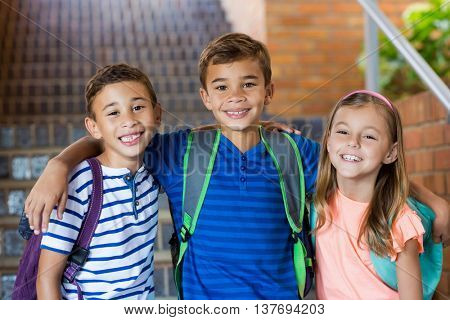 Portrait of smiling school kids standing with arm around at school