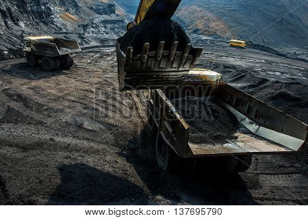 An excavator loading big truck with coal in open pit