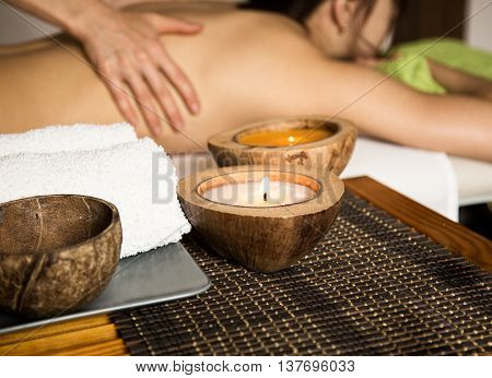 Young woman receiving a back massage in the spa salon. close-up of a candle and towels. woman with eyes closed lying on massage table at salon.