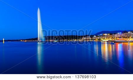 The famous national landmark Jet d'eau as seen from Jardin Anglais on a summer night. To the right is the Eaux-vives waterfront