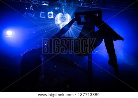 Beautiful woman performing pole dance. Shot with stage lighting background and mirror ball