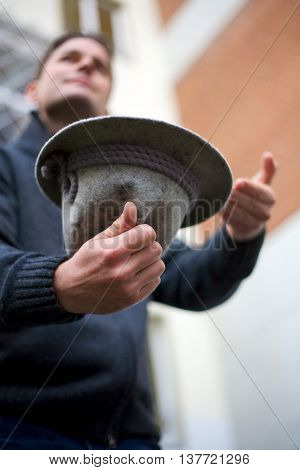 Blurred white man collecting donations with grey hat that is focused.