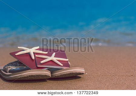 Travel, holiday and vacation in the summer tranquility and relaxation getaway concept. Flip flops with passports and starfish on the sand beach with blue sea ocean in the background