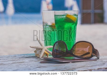 Holiday travel vacation summer on the beach near the sea with cocktails concept. Passports with starfish and sunglasses on wooden table at the beach and blue sea ocean and sand beach in the background