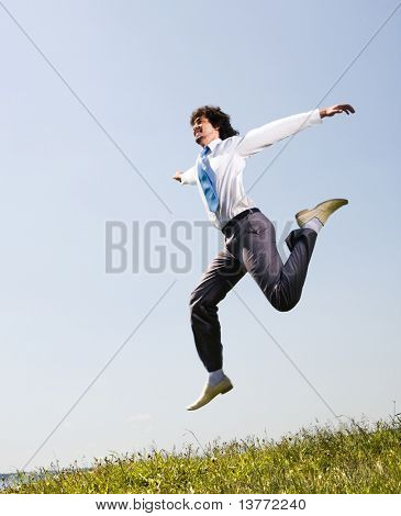 Portrait of happy employee jumping and raising hands