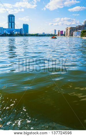 YEKATERINBURG RUSSIA -AUGUST 24 2013. Summer architecture view- business administrative and residential skyscraper buildings on the embankment of Iset river with splashing water on the foreground