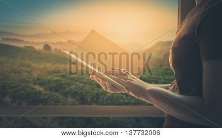 Young woman reading blank book beside window in morning time on weekend with mountain view in blurry background. Weekend lifestyle concept with vintage filter effect