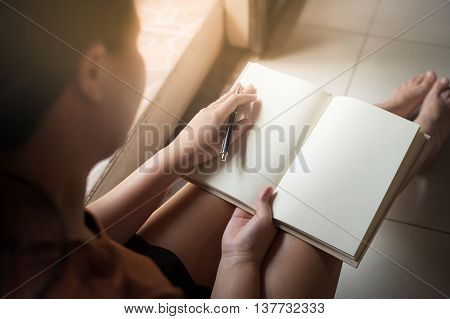 Young woman reading blank book while sitting beside window in morning time on weekend. Morning lifestyle on weekend concept.
