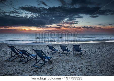 Six deckchairs on the beach with bright sun and waves