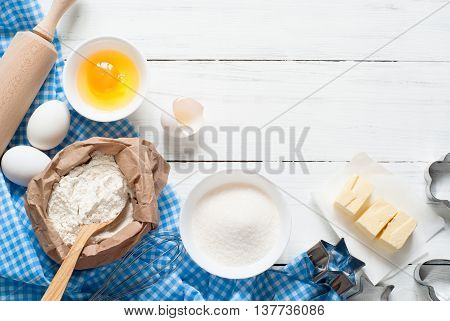 Ingredients for cooking baking - flour, egg, sugar, rolling pin on white wooden table.