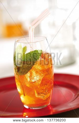 Orange cocktail served with ice and mint leaves.