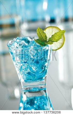 Blue mojito cocktail made with sugar lime juice mint leaves soda white rum and blue curacao.