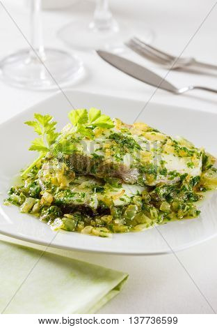 Fried hake slices in a parsley and garlic sauce