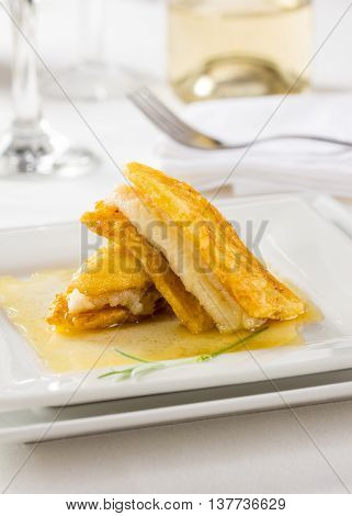 Sole fish fillet served with banana an a sauce.
