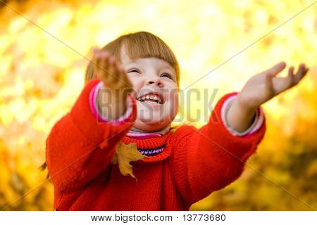 Cute girl laughing and playing with autumn leaves in park