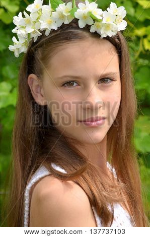 The young girl on nature with a wreath of jasmine
