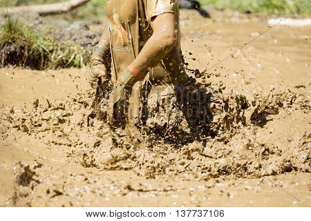 A participant is jumping into muddy water at an extreme sport challenge near Sofia. The sports event is mud and obstacle course designed to test people's physical strength stamina and mental grit.